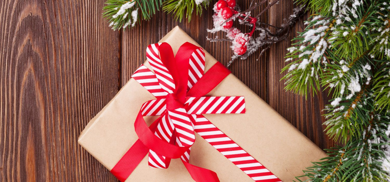 46377155 - christmas gift box and snow fir tree on wooden background